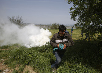 Man runs away from tear gas during scuffles between migrants and refugees and Macedonian police near a makeshift camp at the Greek-Macedonian border near the village of Idomeni