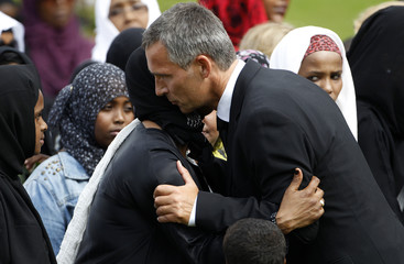 Norway's Prime Minister Stoltenberg comforts a relative of Mona Abdninur during her funeral ceremony in Hoeybraeten
