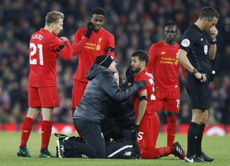 Liverpool's Kevin Stewart receives medical attention after sustaining an injury