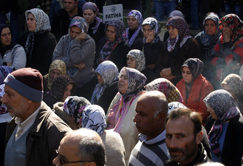People attend the funeral of a victim who died during an explosion at a crossing on Turkey's border with Syria, in the town of Reyhanli