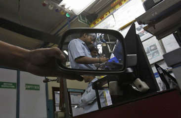 An employee checks a side-view mirror of a vehicle at a factory of the Samvardhana Motherson Group in Noida