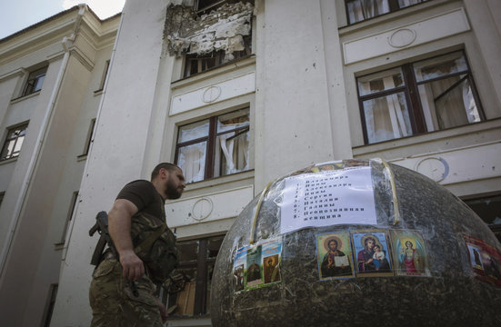 Armed pro-Russian separatist walk past religious icons and list of victims placed in front of a regional administration building damaged by recent explosion in the eastern Ukrainian city of Luhansk