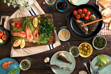 Dinner table with shrimp, fish grilled, salad, snacks and wine