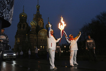 Zhigunova, an empolyee of Baltika Breweries company, and jazz saxophonist Butman take part in Sochi 2014 Winter Olympic torch relay in front of the Church of the Savior on Spilled Blood in central St. Petersburg
