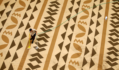 A worker cleans a deck on Waikiki Beach in Hawaii