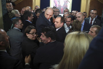 Kosovo opposition MPs tussle with security personnel to enter the assembly room before releasing tear gas, in Pristina