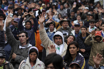 Peasant supporters of Paraguay's President Lugo raise their hands as they pray for him in the plaza outside the National Congress before the start of Lugo's impeachment in Asuncion
