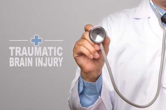 "Doctor holding a stethoscope and word ""traumatic brain injury"" Immune System as medical concept."