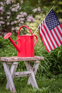 Red watering can with American flag on shabby white potting bench in garden