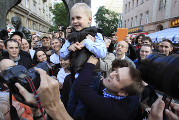 Prominent anti-corruption blogger and opposition leader Navalny lifts his son Zakhar during a meeting with his supporters in central Moscow
