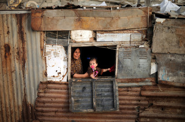 Palestinian woman and her child look out of the window of their shelter in Deir al-Balah refugee camp in the central Gaza Strip