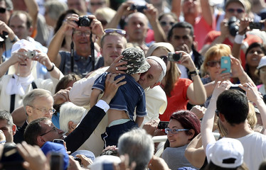 Pope Francis kisses a child as he arrives at his weekly general audience at St. Peter's Square at the Vatican