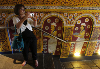 A tourist takes pictures in side the Sri Dalada Maligawa in Kandy
