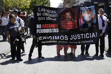 Journalists hold a sign and take part in a protest against the killing of two journalists on March 10 in Mazatenango, south of Guatemala City
