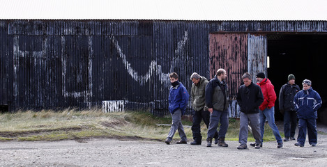 Argentine Falklands War veterans walk out of an old barn that was used as a prision for Argentine soldiers during the Falklands War west of Port Stanley