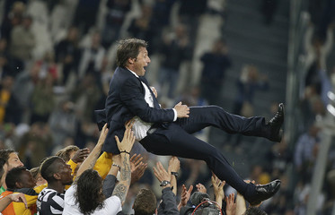 Juventus' players throw their coach Conte in the air after winning the Serie A championship at the end of their match against  Atalanta at the Juventus stadium in Turin