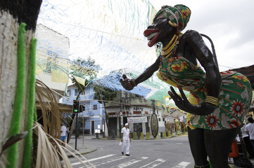 A man walks near a statue of an African woman placed to celebrate the World Cup, at the Engenho de Dentro neighborhood in Rio de Janeiro
