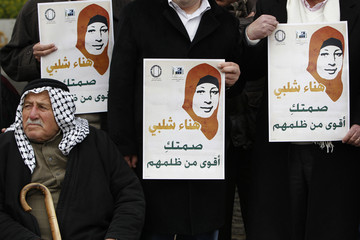 Palestinians hold pictures of prisoner Hana Shalabi, during a protest in support of Shalabi outside the Red Cross building in East Jerusalem