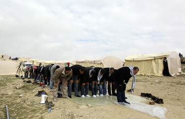 Palestinians pray near newly erected tents in an area known as E1, near Jerusalem
