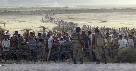 File photo of Turkish soldiers standing guard as Syrians wait behind the border fences near the southeastern town of Suruc in Sanliurfa province