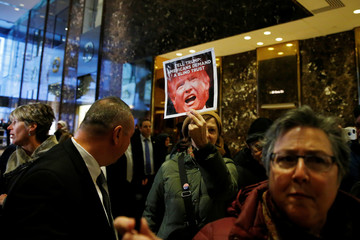 Demonstrators march in the lobby of Trump Tower in Manhattan, New YorK
