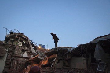 A man looks at the rubbles of a three-storey factory building, which collapsed on Monday in Lahore