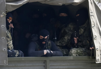 Armed men, wearing black and orange ribbons of St. George - a symbol widely associated with pro-Russian protests in Ukraine, drive a car in Slaviansk