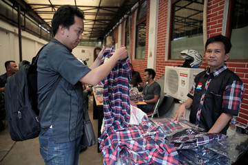 A supporter of the governor of Indonesia's capital Basuki Tjahaja Purnama (L) holds a checkered shirts in red, white and blue before buying it in Jakarta