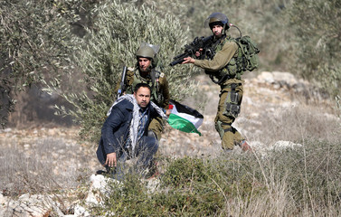 Israeli soldiers detain a Palestinian protester during clashes following a protest against the near-by Jewish settlement of Qadomem, in the West Bank village of Kofr Qadom near Nablus