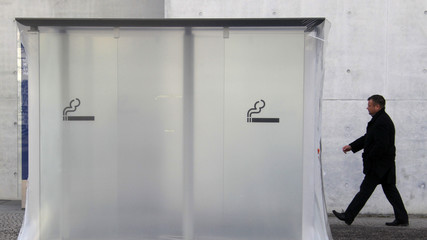 A man walks past a smoking cubicle pictured outside Marie-Elisabeth-Lueders-Haus building in Berlin