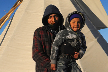 David Red Bear and his son Kazlin Red Bear, from the Standing Rock Sioux tribe pose for a photograph in an encampment during a protest against plans to pass the Dakota Access pipeline near the Standing Rock Indian Reservation, North Dacota