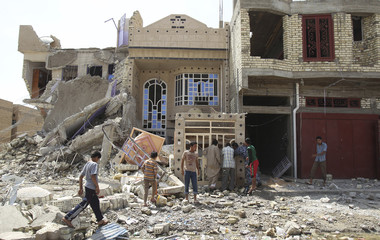 Residents inspect a destroyed building at the site of a bomb attack in Chukook district in northwestern Baghdad