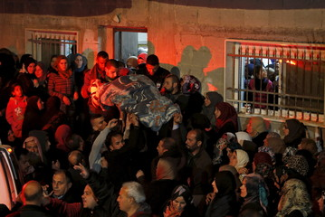 Mourners carry the body of Palestinian woman Amani Sabateen during her funeral south of the West Bank city of Bethlehem