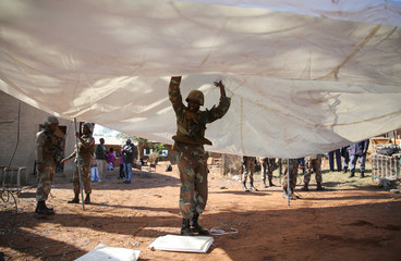 SANDF member helps set up a tent to be used as a polling station in Vuwani