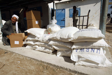 Palestinian man sits next to sacks of flour received from UNRWA in Khan Younis