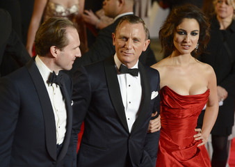 """Actors Daniel Craig and Ralph Fiennes, and actress Berenice Marlohe, pose for photographers as they arrive for the royal world premiere of the new 007 film """"Skyfall"""" at the Royal Albert Hall in London"""