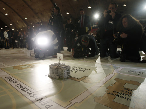 News photographers take pictures of a model of the White House on a large map at the DC Armory in Washington