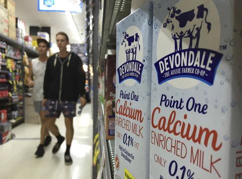 Shoppers walk past cartons of Devondale UHT long life milk at a Sydney supermarket,