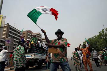 Anti-government protester waves a flag during a march in Abuja