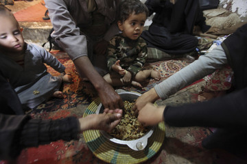 Children eat with their families in their home in Sanaa