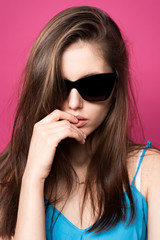 Beautiful fashionable woman in black sunglasses. Pink background. Girl in sunglasses.