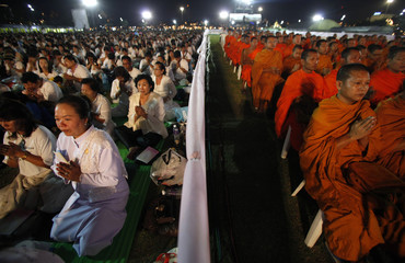 Thais and Buddhist monks pray during a Buddhist ceremony for good luck during their 2012 new year celebrations at Sanam Luang park in Bangkok