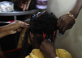 A woman has hair extensions of a style called Megahair at a hair salon in a local market in Rio de Janeiro