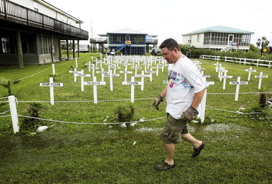 Patrick Shay, a seafood business owner from River Ridge, walks past grave sites that he and his neighbors built at their fish camp in Grand Isle