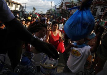 Survivors of Typhoon Haiyan line up to get food and water during a disaster relief operation run by an NGO in Tacloban
