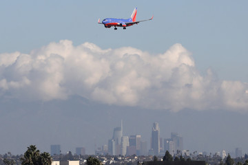 A Southwest plane flies into LAX airport past downtown Los Angeles