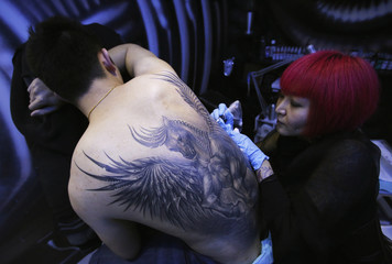 Tattoo artist Sun Lan tattoos image of horse with wings on back of her client Li Sheng at her studio ahead of upcoming Chinese lunar New Year in Beijng