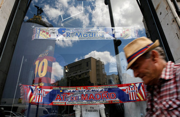 A man walks by a store displaying souvenirs of the UEFA Champions League Final between Atletico Madrid and Real Madrid in downtown Madrid