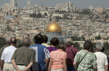 Tourists on the Mount of Oliveslook at a view of Jerusalem's Old City