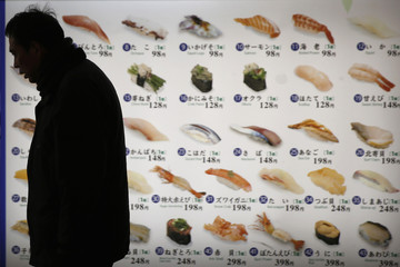 Man walks past images of sushi displayed outside a sushi restaurant in Tokyo